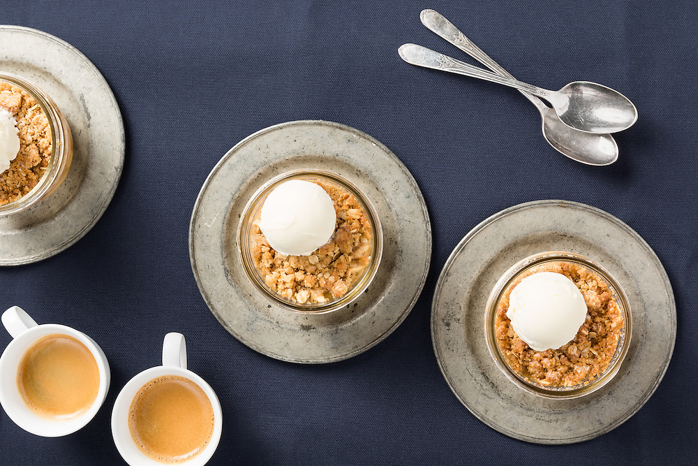 An overhead view of apple crisp in glass jars with spoons and cups of espresso.