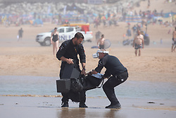 © Licensed to London News Pictures. 31/07/2020. Newquay, UK. Police move drone equipment on Fistral Beach, Cornwall, after being splashed by a wave on a very hot day in the southwest. Parts of the country are expected to have the hottest day of the year so far. Photo credit : Tom Nicholson/LNP