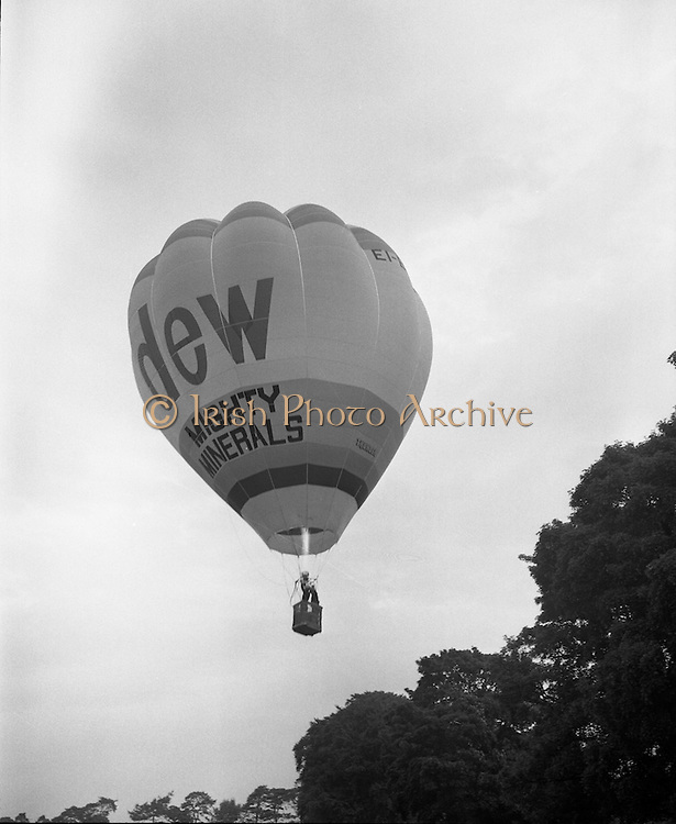 Dew Mighty Minerals Hot Air Balloon.   (H15)..1974..07.08.1974..08.07.1974..7th August 1974..The launching of the Dew Mighty Minerals hot air balloon,took place in Tullamore,Co Offaly last night,as part of the Tullamore Festival Week. The balloon was piloted by Mr Wilf Woollett,a veterinary surgeon from Loughrea,Co Galway and his co-pilot was Kevin Haugh. Miss Rosemary Mannion,the Offaly Rose of Tralee contestant sent the balloon on its way by popping a bottle of Champagne over it.  The balloon itself has a capacity of 56,000 cubic feet,is 60ft high and 50ft wide. It is made from nylon/polyproplene. The basket is 2ft square by 3ft high and carries two people,it is attached to the balloon by steel cables..Wilf Woollett has piloted the balloon in the U.S. and Britain and is a member of the Dublin Balloon Club...Up Up and Away the balloon is pictured being powered upwards by the gas burner.