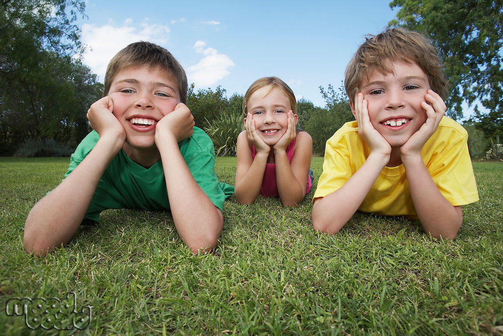 Portrait of two boys and girl (6-11) lying on grass leaning on elbows