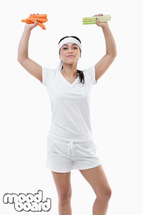 Portrait of young sportswoman with arms raised holding carrots and celery over white background