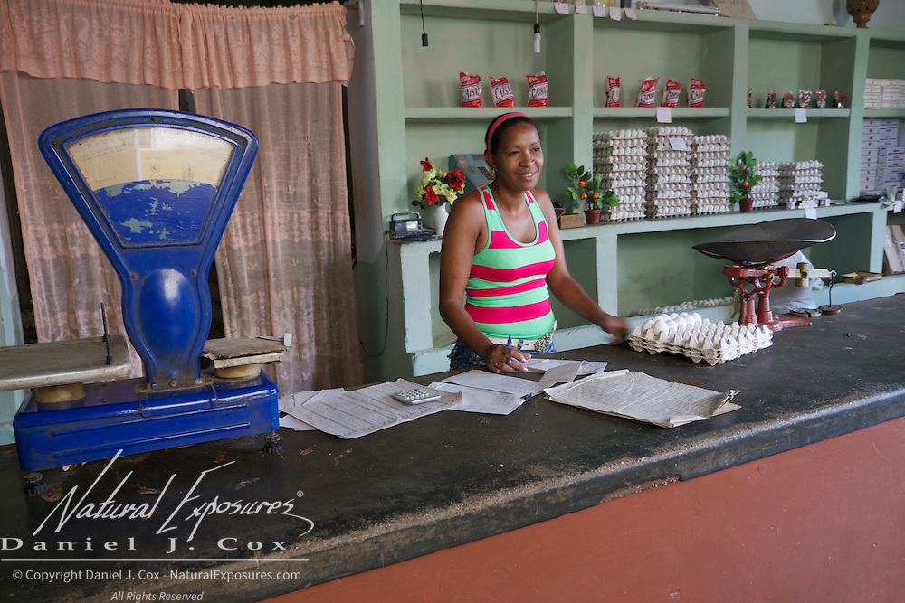 A woman who runs one of the Cuba government's food ration stores waits for local residents to come in for some of their monthly food items such as the eggs on the counter.