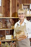 Portrait of a happy senior employee holding bread in market
