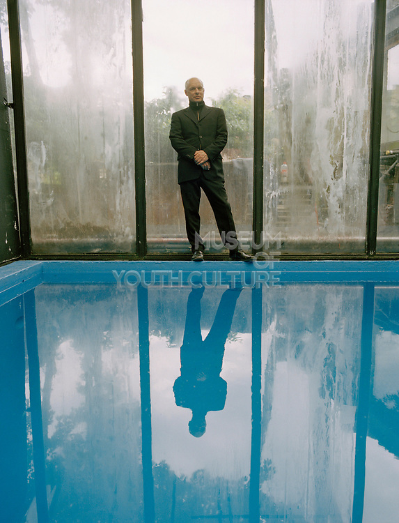 Man standing on the edge of an indoor pool.