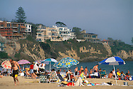 Luxury Homes on cliffs above summer crowds of people and umbrellas on sand beach at Corona Del Mar, Newport Beach, Orange County, California