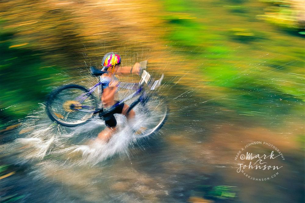 Woman carrying her Mountain bike across stream, Queensland, Australia