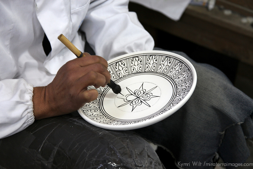 Africa, Morocco, Fes. Moroccan artisan hand paints ceramic plate.