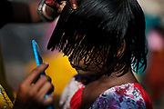Sangita Jatev, 38, is brushing the hair of her daughter Poonam, 9, while in the front yard of their newly built home in Oriya Basti, one of the water-contaminated colonies in Bhopal, central India, near the abandoned Union Carbide (now DOW Chemical) industrial complex, site of the infamous '1984 Gas Disaster'.