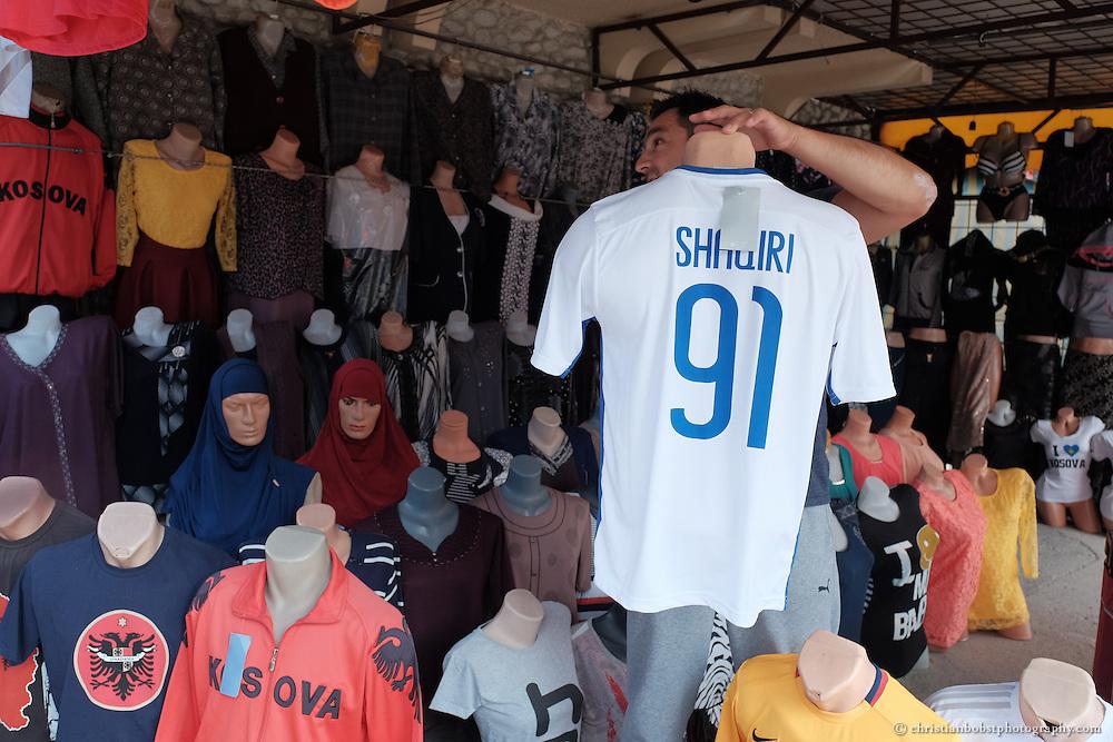 Ein Kleiderverkäufer mit einem Shaquiri Fussball Shirt in einem Laden in der kosovarischen Stadt Peja