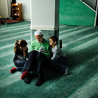 Muslim man reading a religious text, accompanied by a boy and a girl in the room that serves as a prayer hall and makeshift mosque on an industrial estate in the town of Wil. Their community's project to build a cultural centre including a minaret was one of the two propositions that sparked a controversial anti-minaret campaign that led to a referendum banning minarets in Switzerland.