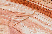 Red, yellow, and white sandstone erodes into fascinating shapes in the White Domes area in Valley of Fire State Park, Nevada, USA. Starting more than 150 million years ago, great shifting sand dunes during the age of dinosaurs were compressed, uplifting, faulted, and eroded to form the park's fiery red sandstone formations. The park also boasts fascinating patterns in limestone, shale, and conglomerate rock. The park adjoins Lake Mead National Recreation Area at the Virgin River confluence, at an elevation of 2000 to 2600 feet (610-790 m), 50 miles (80 km) northeast of Las Vegas, USA. Park entry from Interstate 15 passes through the Moapa Indian Reservation.