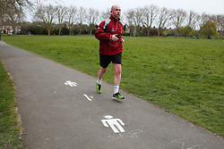 © Licensed to London News Pictures. 01/04/2020. London, UK. A jogger jogs past social distancing marks on the pathway at a north London park as coronavirus lockdown continues. Photo credit: Dinendra Haria/LNP