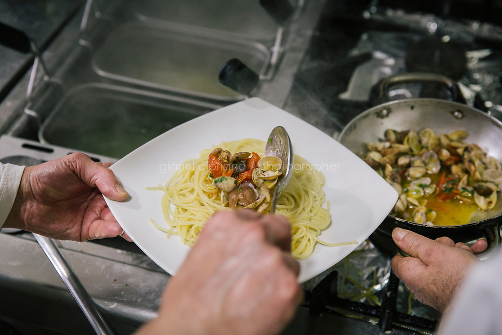 NAPLES, ITALY - 20 MARCH 2018: Raffaele Esposito prepares a spaghetti with clams sauce dish in the kitchen of the Pizzeria e Trattoria Vigliena in Naples, Italy, on March 20th 2018.<br /> <br /> Pizzeria e Trattoria Vigliena is a restaurant outside of the city center and adjacent to the port. At lunch, the place is packed with workers from the docks and ship owners and workers from the recently built Marina Vigliena.<br /> <br /> The restaurant is owned by Raffaele Esposito, Concetta&rsquo;s son and the third generation of a family of chefs who founded this restaurant in the middle of the 20th century