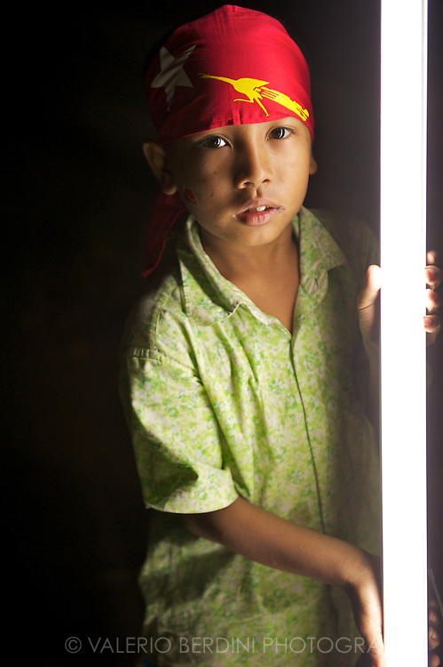 A child holds a neon light helping to mount a stall to support the NLD campaign in the last night before the elections. Mandalay, Myanmar. 2012