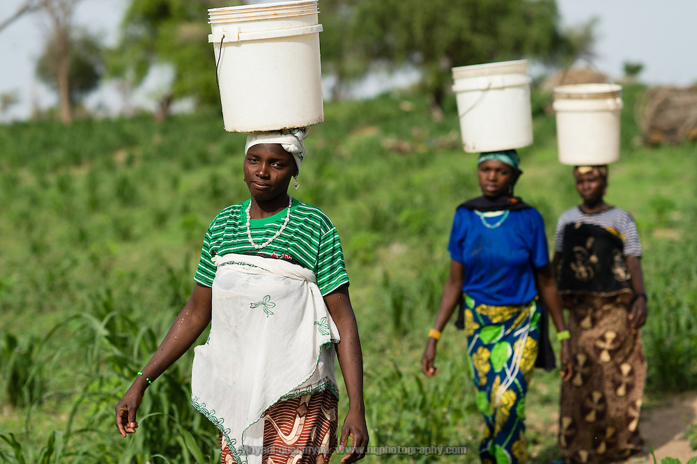 "Koumsa Maman, 25, carrying water home from a WaterAid pump in the village of Kanwa-Maraki in the Zinder Region of Niger on 25 July 2013. When asked about the pump as compared to the villages previous water source she said, ""The water tastes good, and there is no risk of sickness when you drink it."""