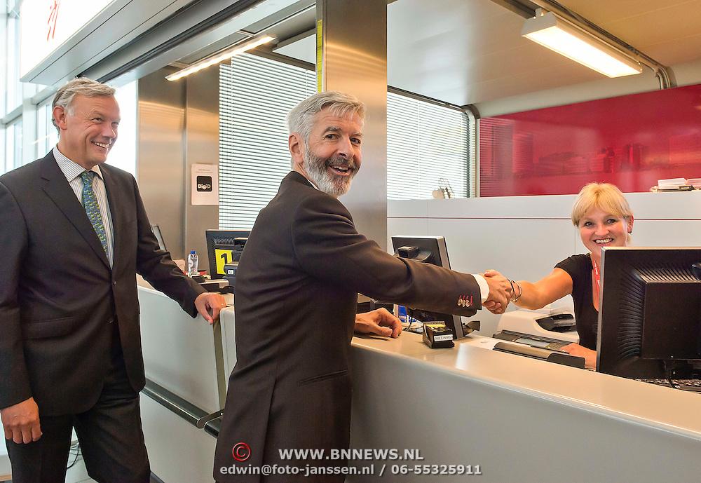 Schiphol 13-08-2013. Minister Plasterk ( Binnenlandse Zaken en Koninkrijkrelaties) opende vanmiddag op Schiphol een gemeentebalie waar Nederlanders die in het buitenland wonen een paspoort en een DigiD kunnen aanvragen. Ook inwoners uit Haarlemmermeer kunnen bij de balie terecht voor het aanvragen van een paspoort of identiteitskaart. Foto: president en CEO Schiphol Group Jos Nijhuis kijkt toe als minister Plasterk een baliemedewerkster op Schiphol begroet.