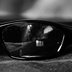 A brick wall and security light are reflected in a closeup of black sunglasses.