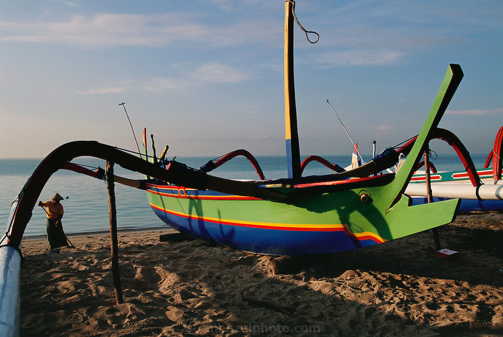 Brightly painted wooden boats on Sanur Beach, Bali, Indonesia. At sunrise a woman rakes the beach before tourists arrive.