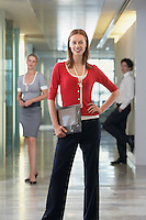 Businesswoman standing in office corridor with others portrait