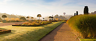 A hot air balloon rises over the lake at Trentham Gardens, Staffordshire, while the early morning sun illuminates the Italian Garden, featuring fastigate Irish yews, herbaceous borders and planters containing Portuguese laurels (Prunus lusitanica). Photographed in October.