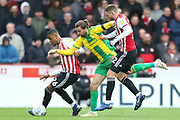 West Bromwich Albion forward Jay Rodriguez (19) battles for possession with Brentford defender Ezri Konsa (26) and Brentford defender Henrik Dalsgaard (22) during the EFL Sky Bet Championship match between Brentford and West Bromwich Albion at Griffin Park, London, England on 16 March 2019.