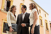Two businesswomen and one businessman standing outdoors low angle view.