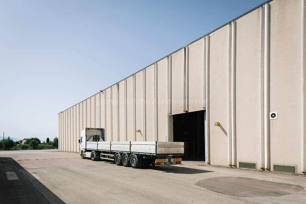 SANTA MARIA DEGLI ANGELI (ASSISI), ITALY - 11 JUNE 2018: A truck is seen here by the entrance of IRON S.p.A., a publicly traded company that makes industrial steel parts, in Santa Maria degli Angeli (Assisi), Italy, on June 11th 2018.<br /> <br /> President Donald Trump&rsquo;s administration plans to impose tariffs on European steel and aluminum imports after failing to win concessions from the European Union, a move that could provoke retaliatory tariffs and inflame trans-Atlantic trade tensions. Until the moment that the American president rendered his decision, Mr. Capponi, the commercial director of IRON spa, was confident the continent would be spared.<br /> Given that IRON is a purchaser of steel, the company might benefit from the American tariffs. Steel now shipped to the United States from mills within Europe might stay here to avoid the tariffs, raising the supply and dropping prices. Chinese producers who export to American shores could divert their product to Europe, amplifying this trend.<br /> But Mr. Capponi was banking on none of this. Even if steel prices decline, his customers are likely to squeeze him for lower prices. More broadly, the American tariffs &mdash; justified by the Trump administration as a supposed defense of national security &mdash; reverberated as a blow against world trade.