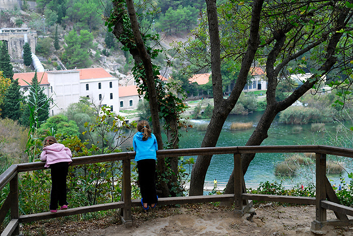 Two children (9 years old, 5 years old) at lookout overlooking lake and powerstation, Krka National Park, Croatia