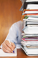 Man writing close-up of arm and hand sitting behind stack of paperwork at desk