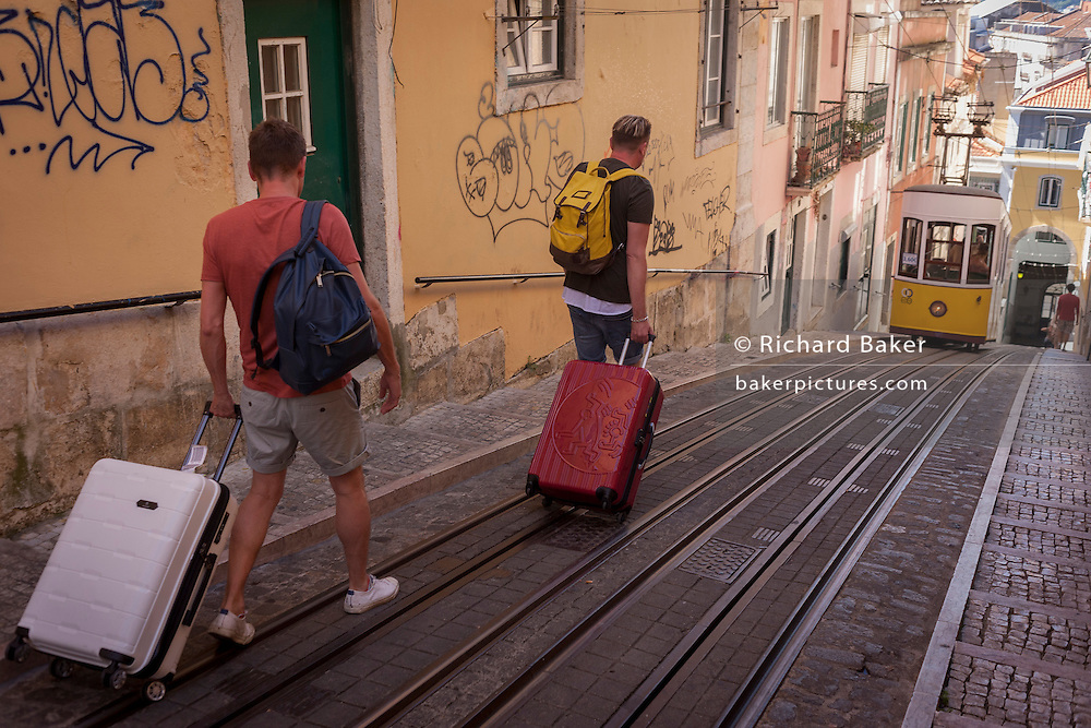 Two tourists walk downhill with their baggage towards one of the two cars of the funicular railway climbing the steep gradient of on Rua de Bica de Duarte Belo (Elevador da Bica), on 13th July 2016, in Lisbon, Portugal. The mechanical motor of the elevator was installed in 1890, but the lift only began functioning on 28 June 1892, after a couple of years of tests. The Bica Funicular is a funicular railway line in the civil parish of Misericórdia, in the municipality of Lisbon, Portugal. It connects the Rua de São Paulo with Calçada do Combro/Rua do Loreto, operated by Carris. (Photo by Richard Baker / In Pictures via Getty Images)