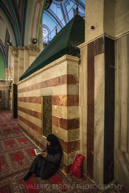A muslim woman sits with the Koran next to the Tomb of Leah, Isaac's wife inside the Ibrahim (Abraham in Arabic) Mosque. Three prophets and their wives are buried in the place. Isaac and Leah are only accessible from the Mosque, Abraham and Sarah visible from both sides, Jacob and Rebecca lie in the Jewish only part of the building.