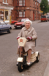 Elderly woman travelling down street on mobility scooter,