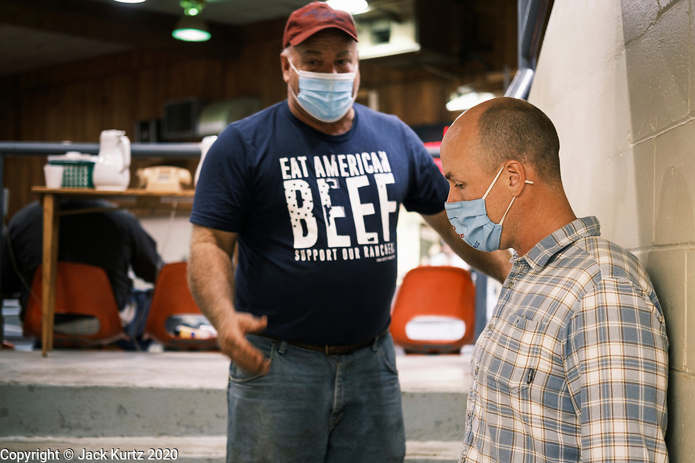 """22 SEPTEMBER 2020 - DUNLAP, IOWA: Congressional candidate J.D. SCHOLTEN (right) talks to JON SCHABEN, a co-owner of Dunlap Livestock Auction, about farm policy. Scholten, a Democrat from Sioux City, Iowa, ran against incumbent CongressmanSteve King (R-4th District Iowa) in 2018 and came within a few percentage points of upsetting the long serving conservative. King lost to Randy Feenstra, a Republican challenger, in the 2020 primary and Scholten is running against Feenstra in the 2020 general election on November 3. Iowa's 4th district, centered in the agricultural and sparsely populated northwest corner of the state, is the largest congressional district in Iowa and encompasses about ⅓ of the state of Iowa. Scholten is on his """"Every Town Tour 2020."""" He is visiting all 375 towns in the 39 counties in the district.    PHOTO BY JACK KURTZ"""