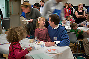 Washington, DC. (October 16, 2009) -- Fathers and kids of the River School celebrate their Friday afternoon with a Dad's hot lunch bunch in the school gym.  The River School provides successful educational experiences for children and their families by uniting the best practices of early childhood education and oral deaf education, and to promote clinical research and training in child language and literacy. The River School is located in Northwest, Washington, DC.  Photo by Johnny Bivera