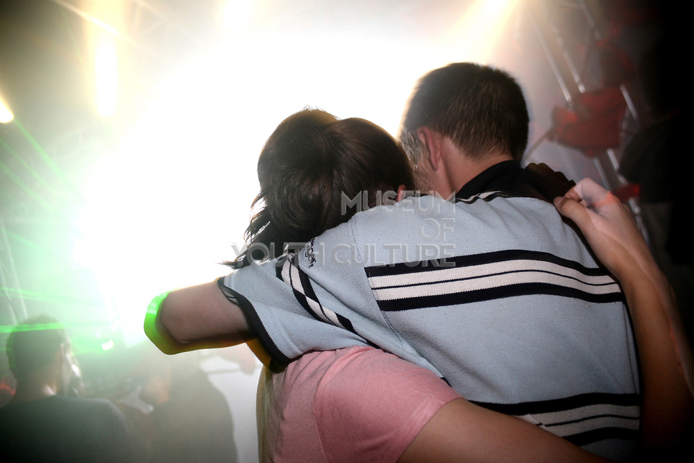 A young couple hug in the dance tent at the Workhouse Festival, Wales, 2006