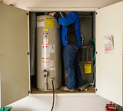 Joe Rosenblum, with Allied Plumbing, stands in a water closet while making an adjustment on an old water heater on Wednesday, March 19, 2014, in Rogers, Ark. Rosenblum was replacing the water heaters in a home in Rogers, Ark. Photo by Beth Hall