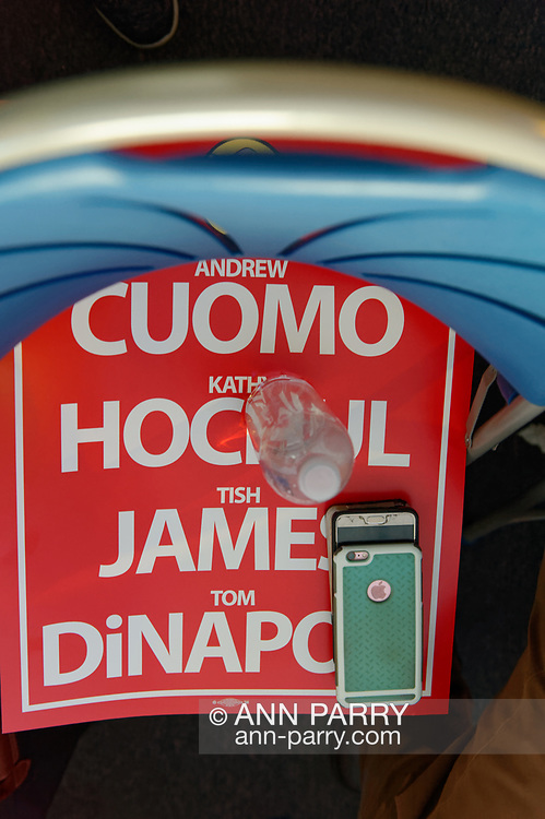 Hempstead, New York, USA. May 23, 2018. Red and white Poster with names of nominees Andrew Cuomo, Kathy Hochul, Tish James, and Tom Di Napoli covers seat of temporarily unoccupied chair during Day 1 of New York State Democratic Convention, held at Hofstra University.