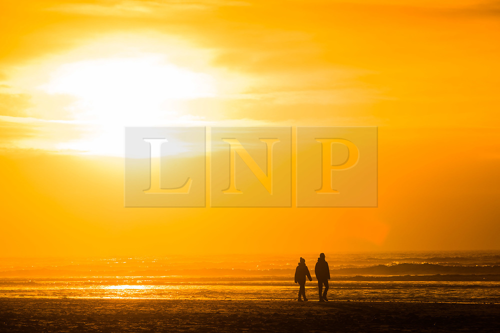 © Licensed to London News Pictures. 1/1/2019. Aberystwyth, UK. People walk along the sandy beach at Ynyslas, near Aberystwyth, west Wales, as the sun sets at the end of the first day of the 2019 new year. Photo credit: Keith Morris/LNP