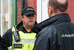 A Police officers from the PSU close side a street in Hexthorpe, Doncaster South Yorkshire  to keep opposing EDL and UAF protester apart. The EDL and UAF are thought to have chosen Hexthorpe after recent media reports of tension between newly arrived Roma residents and the the local community<br /> 18 July 2014<br /> Image © Paul David Drabble <br /> www.pauldaviddrabble.co.uk