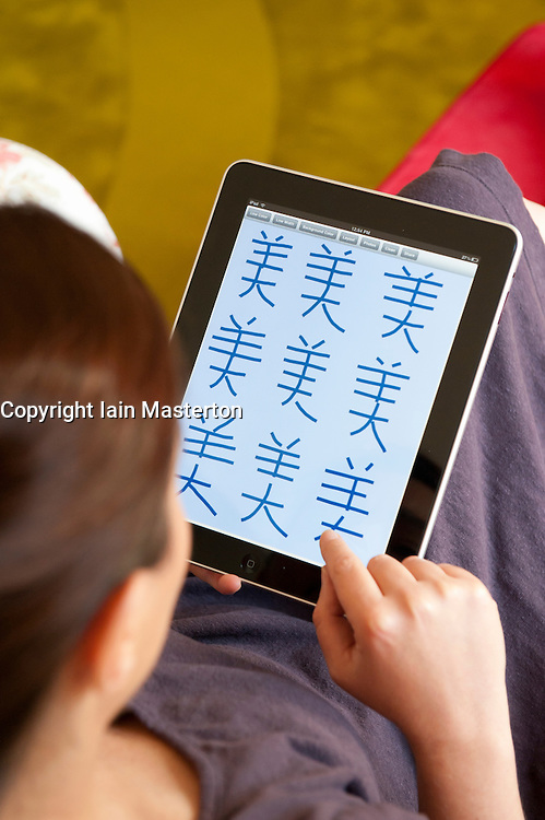 Woman learning to write Chinese characters on iPad tablet computer