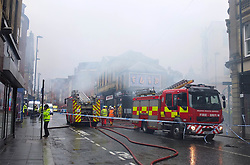 © London News Pictures. 01/12/15. Newscatle, UK. Emergency services at the scene where more than 50 firefighters tackle a blaze in Newcastle city centre today at the Kard Bar on Cross Street. The fire broke out shortly before 9am, with reports of people being trapped on the upper floors. Photo credit: Adam Davies/LNP