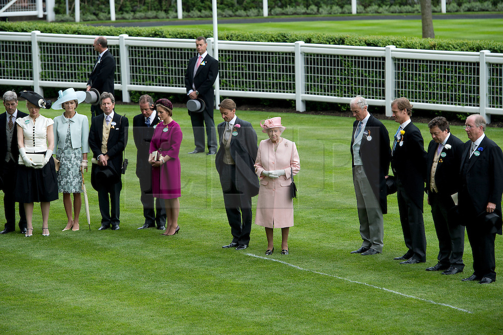 © London News Pictures. 18/06/2013. Ascot, UK.  HRH Queen Elizabeth II (centre) during a one minute silence for Sir Henry Cecil, on day one of Royal Ascot at Ascot racecourse in Berkshire, on June 18, 2013.  The 5 day showcase event,  which is one of the highlights of the racing calendar, has been held at the famous Berkshire course since 1711 and tradition is a hallmark of the meeting. Top hats and tails remain compulsory in parts of the course. Photo credit should read: Ben Cawthra/LNP