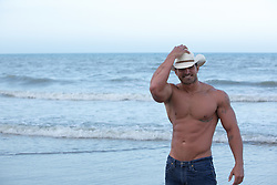 shirtless muscular man in a cowboy hat and jeans at the beach in Florida