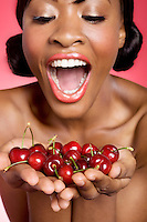 Cheerful young woman looking at cherry in her hands