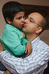 Man holding and kissing his son