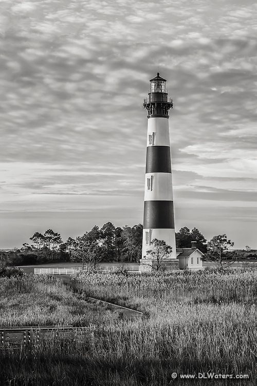 "Black-and-white portrait of bodie Island Lighthouse. Bodie Island Lighthouse stands 156 feet tall and the height of each stripe is 22 feet. It is thought that the island got its name because of the many bodies that washed up from shipwrecks. The inside plaque reads, ""Body Island"". no one is certain how the spelling change came about."
