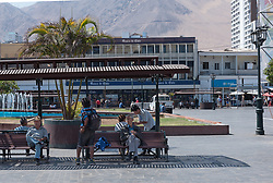 Iquique, Chile—April 9, 2018. Men are resting on benches in the town square of  Iquique, Chile. The foothills of the central mountains are int eh background. Editorial use only.
