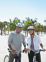 Senior couple on bicycles on tropical beach