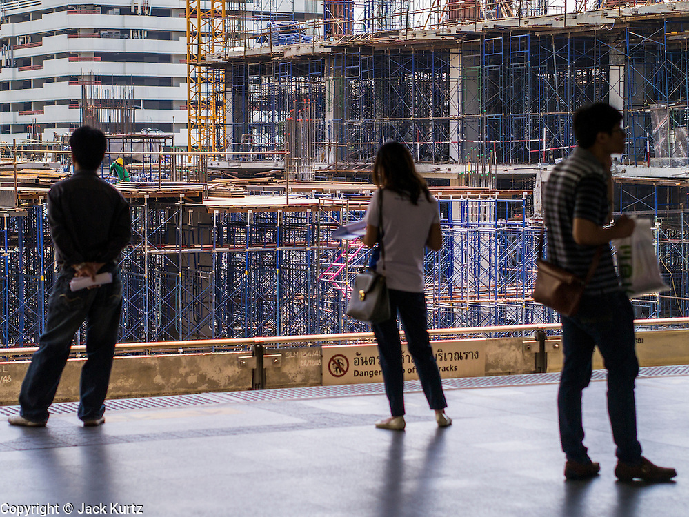 19 APRIL 2013 - BANGKOK, THAILAND:  Construction of a new shopping center in Siam Square frames passengers waiting for an incoming train at the Siam Station of the Skytrain also called the BTS. The system consists of 32 stations along two lines: the Sukhumvit Line running northwards and eastwards, terminating at Mo Chit and Bearing respectively, and the Silom Line which plies Silom and Sathon Roads, the Central Business District of Bangkok, terminating at the National Stadium and Wongwian Yai. The lines interchange at Siam Station and have a combined route distance of 55 km.      PHOTO BY JACK KURTZ