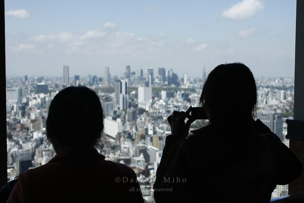 April 11, 2008; Tokyo, Japan - A visitor takes a picture with her camera phone of the view looking north toward Shinjuku from the 39th floor of the Yebisu Tower at Yebisu Garden Place in Ebisu...Photo credit: Darrell Miho